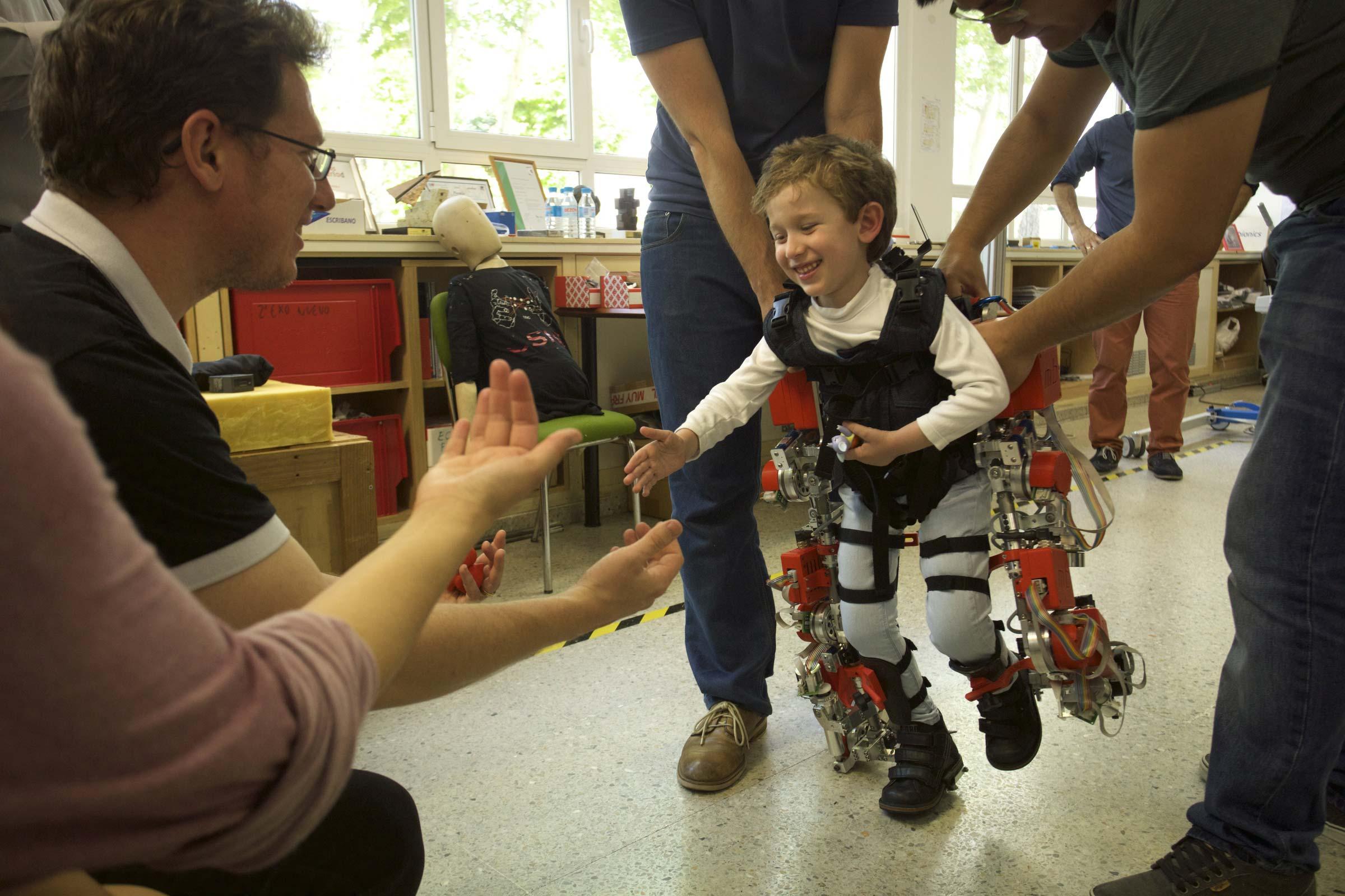 imagen de Álvaro, de cinco años y afectado por atrofia muscular espinal, camina hacia sus padres durante una prueba del exoesqueleto. / Joan Costa – CSIC
